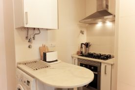 Kitchen island worktop and industrial cooker, fan and oven and gas water heater above worktop