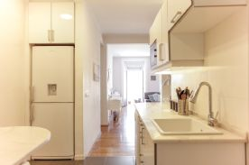 Kitchen view into living area with large fridge inside bespoke cupboard space