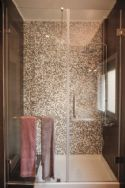 Walk in shower with 2.5m high glass barrier and door.