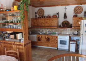 Kitchen, dishwasher, oven, fridge, seen from dining end. Original stone floor.