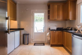 Kitchen with two fridges and freezer. Also includes a washing machine.