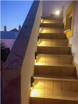 Illuminated stairs leading to the upper terrace.
