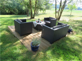 Seating area on wooden decking among the trees.