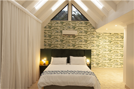 Guest Bedroom 2 features high ceilings and ample space, with small lounge and study area