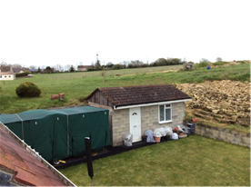 View of outbuilding and additional land for sale.