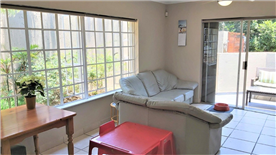 """Open plan """"cottage """"lounge area looking onto patio"""