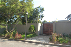 Main gate of house from sidewalk