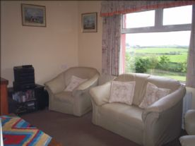 furnished lounge, open fire or black wood stove with garden,rural views to the sea,room size 4.21x2.25.