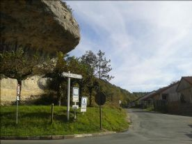 huge splayed overhanging rock and road leading to the house
