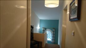 Upstairs hallway leading to stairs with double glazed window looking over terrace.